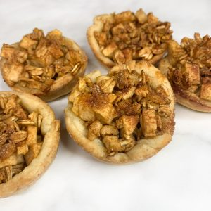 Photo of mini apple pie cups with apple filling in the center of a mini pie crust