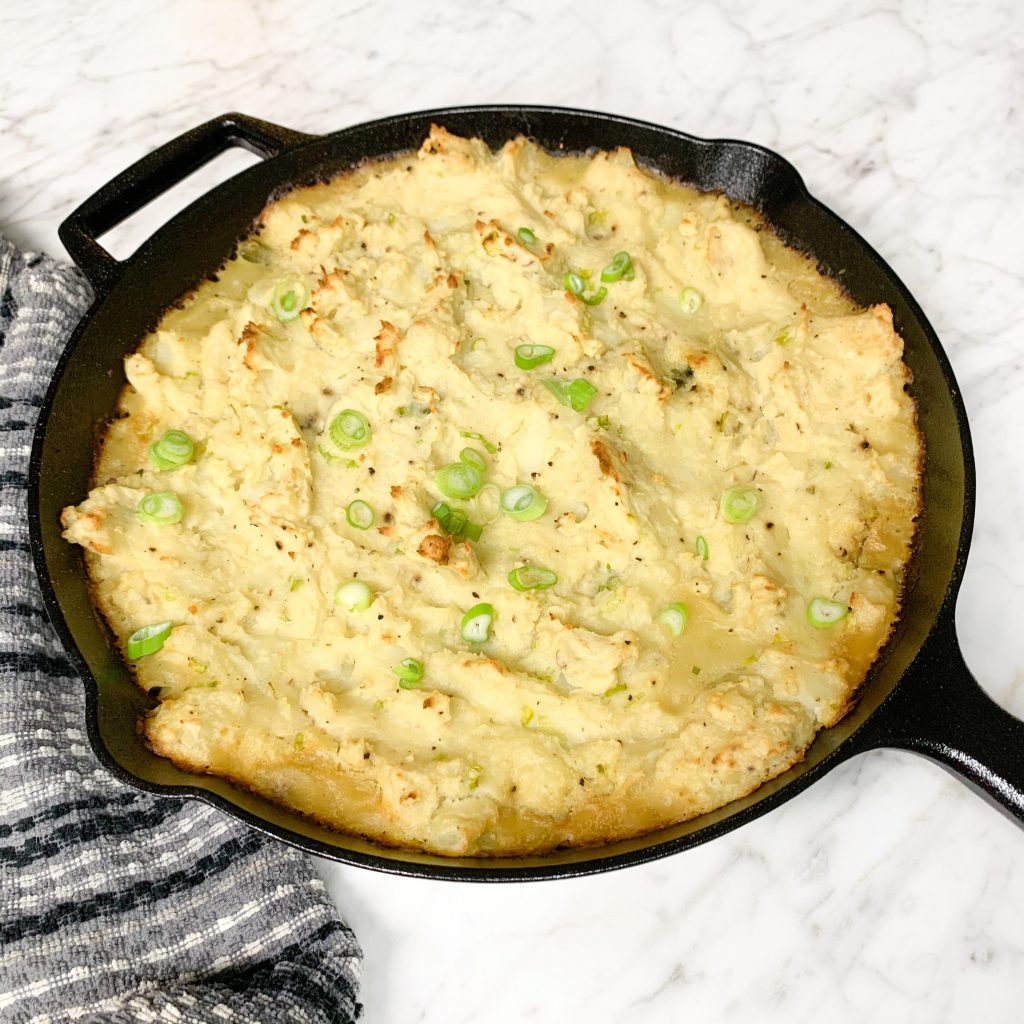 Turkey shepherd's pie in a cast iron skillet topped with chopped green onions