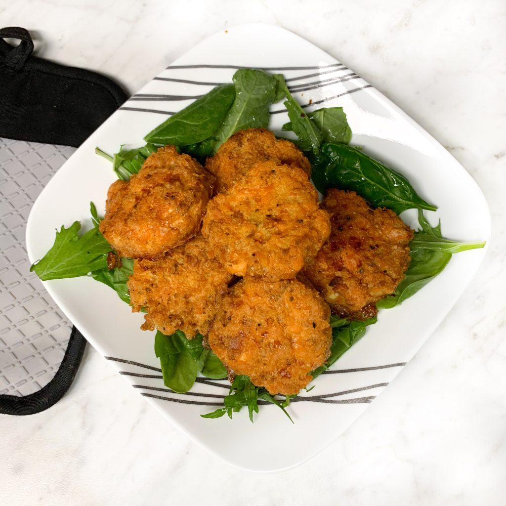 Image of salmon cakes over a bed of mixed greens